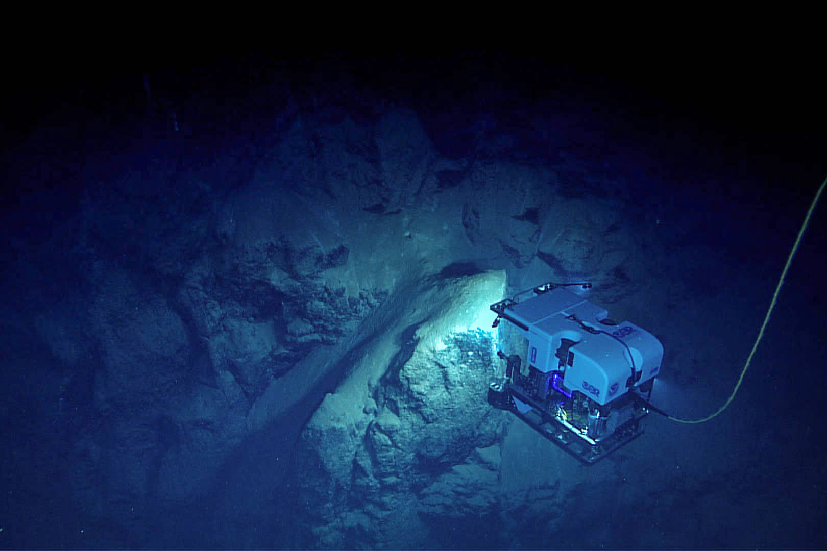 A deep-sea ROV scans an underwater cliff in the Gulf of Mexico.