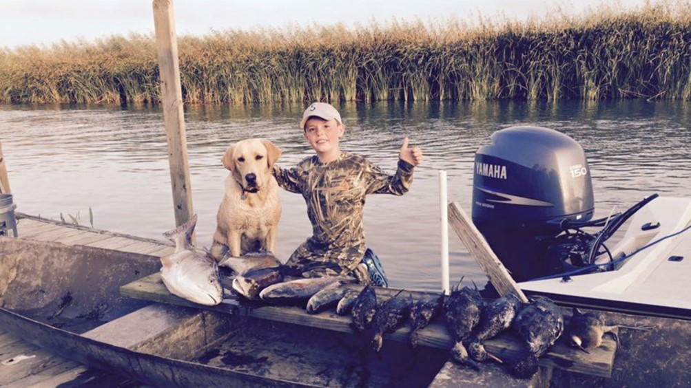 A boy and his dog out recreating on a boat in a marsh in Louisiana.
