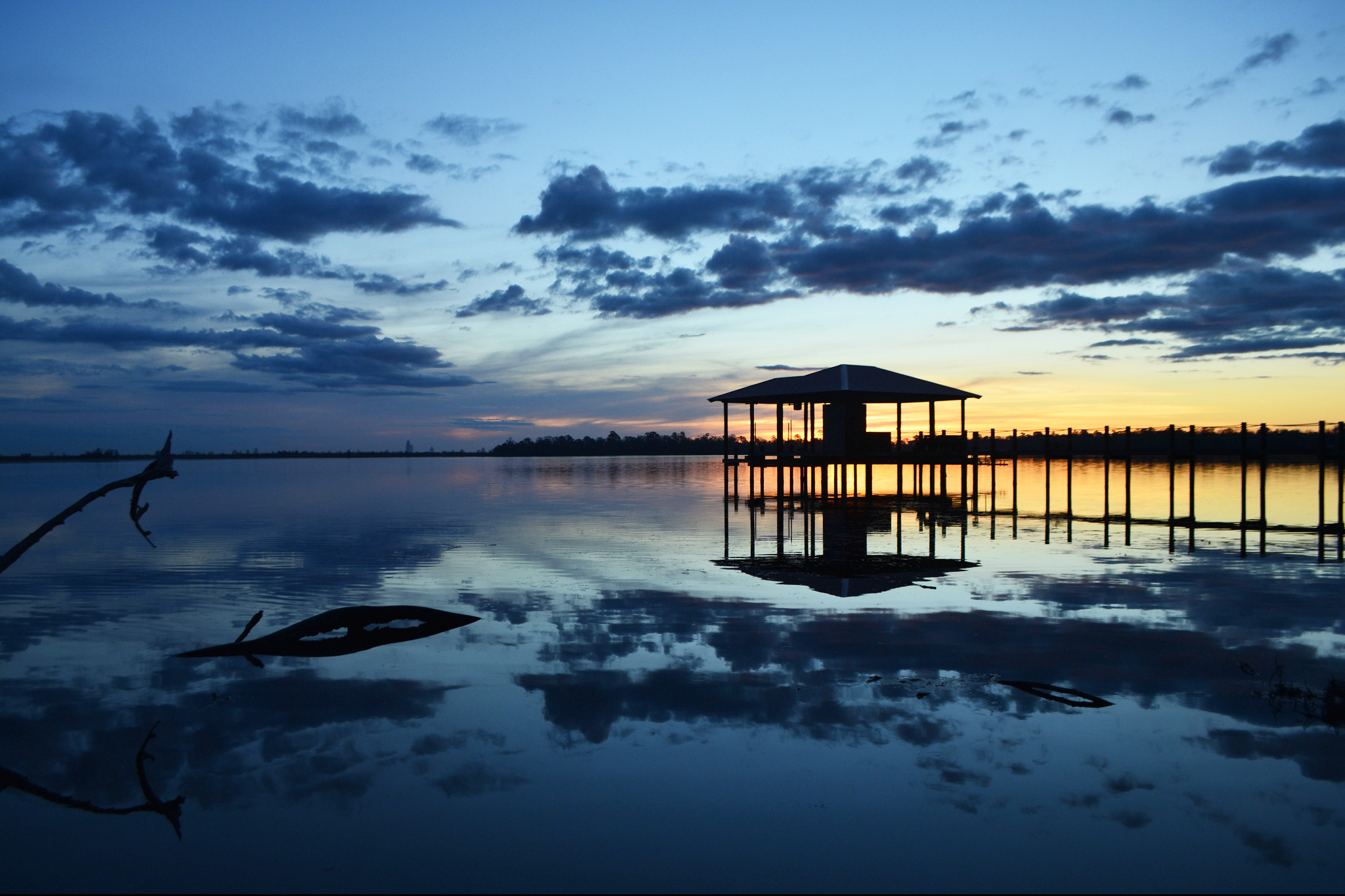 The sun sets across a small bay behind the coastline. A dock and shelter sit above the water in the foreground.
