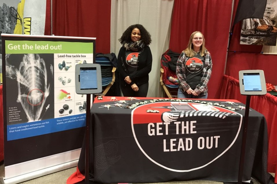 "Two ""Get the Lead Out"" outreach team members in front of a trade show booth."