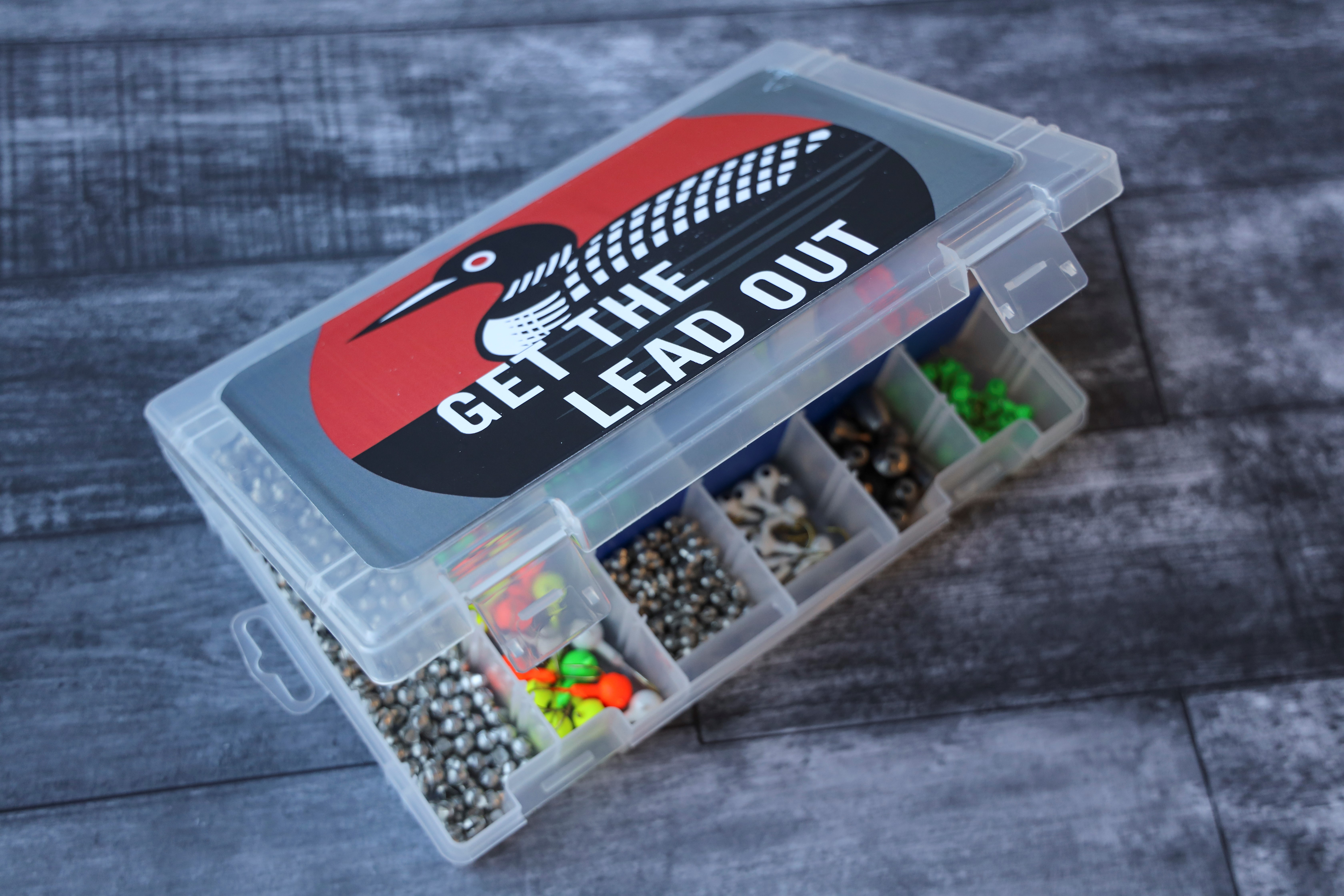 "A small fishing tackle box with a sticker that says ""Get the Lead Out."""
