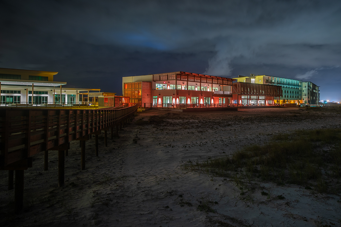 The award-winning Gulf State Park at night. A boardwalk and dunes in the foreground.