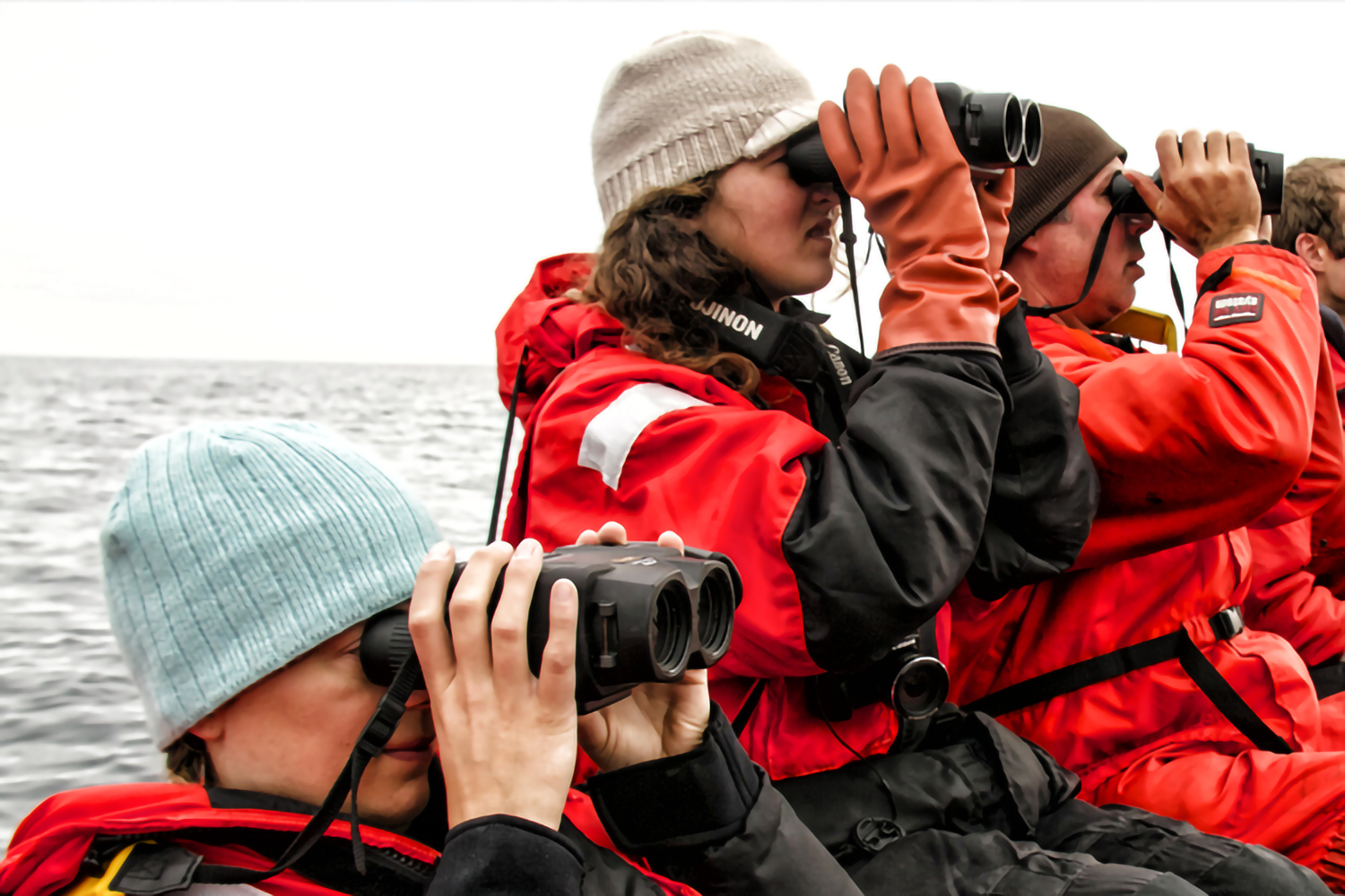 Scientists on a boat observe the ocean with binoculars.