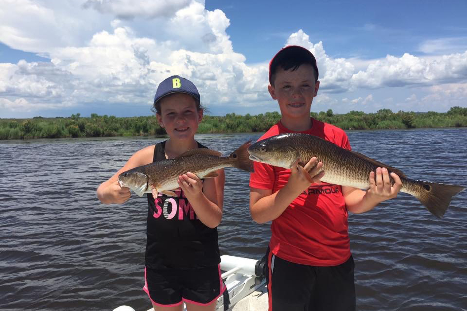 Two kids on a boat hold fish they caught.