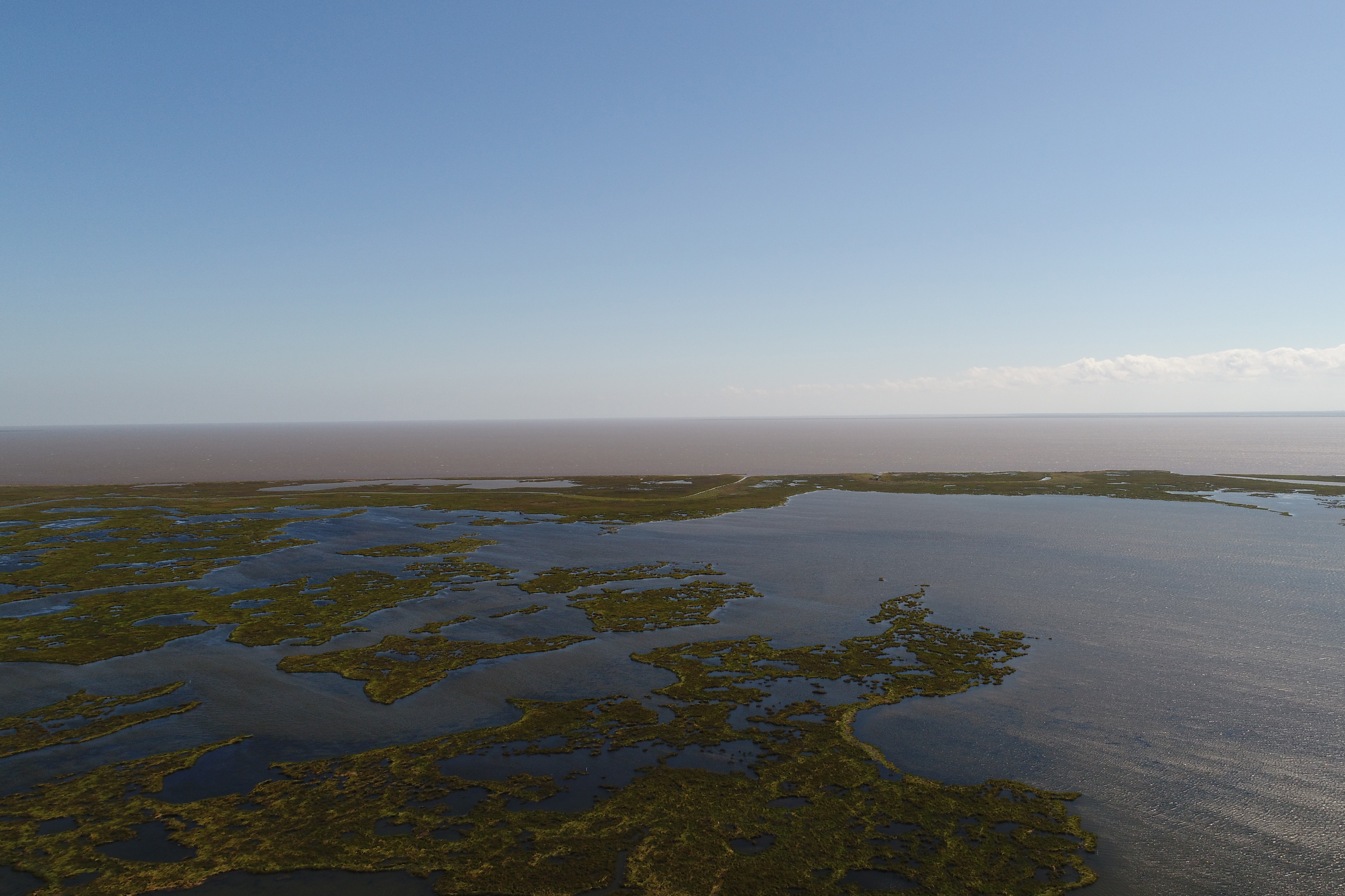 Aerial view of the Golden Triangle marsh restoration area. Green marsh is surrounded by open water in the Gulf of Mexico.
