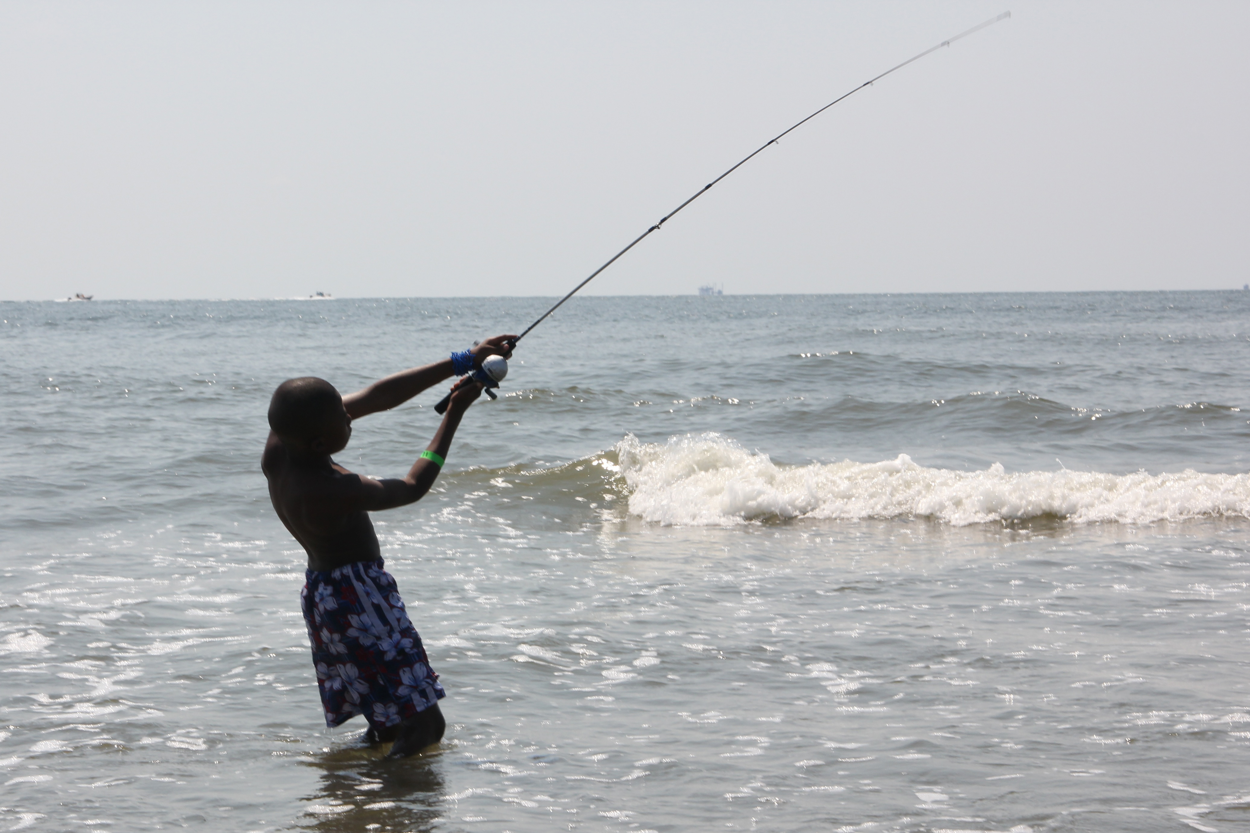 A boy casting with his fishing pole while wading in the water on Elmer's Island beach.