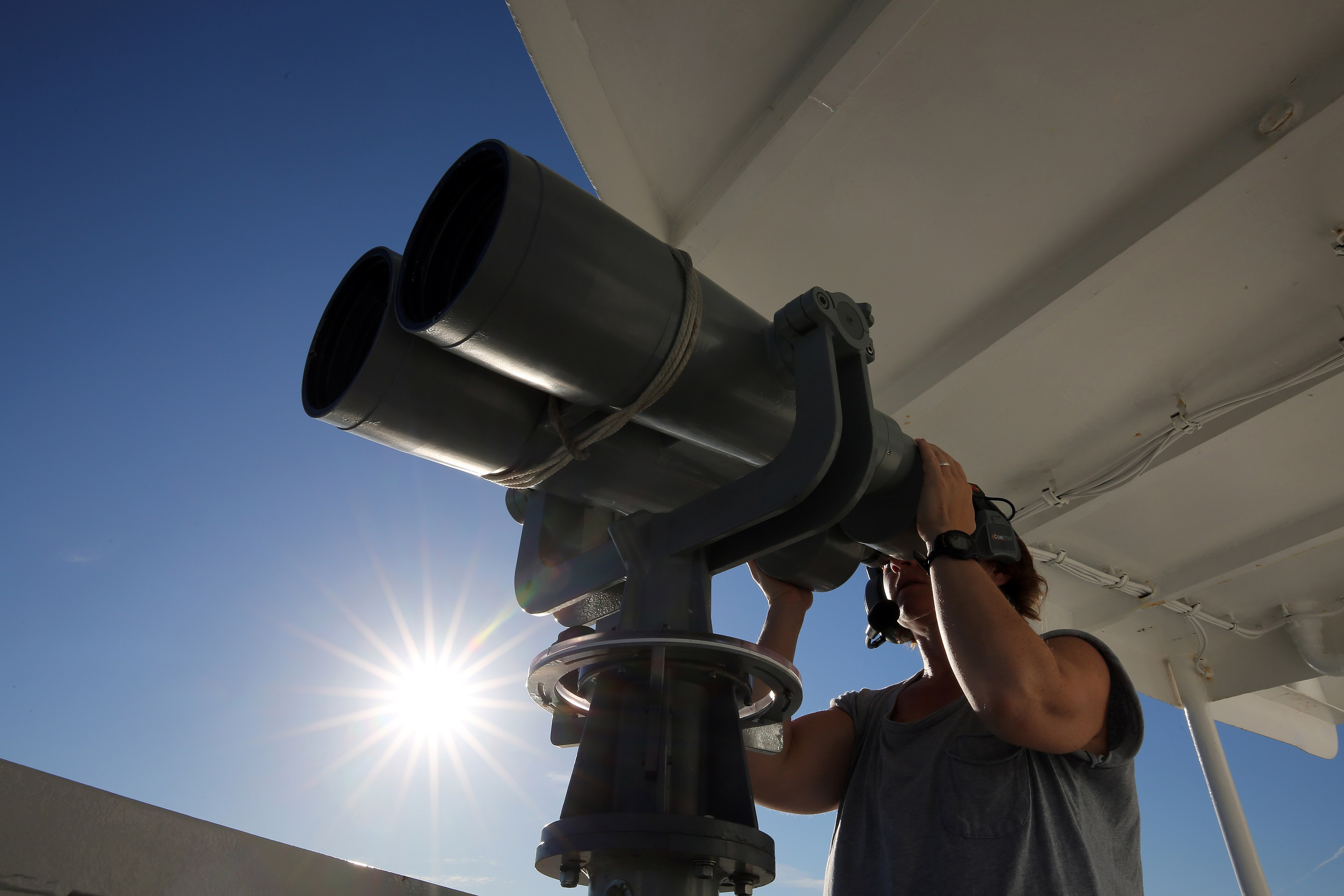NOAA scientist looks through giant binoculars on a ship, looking for marine mammals.