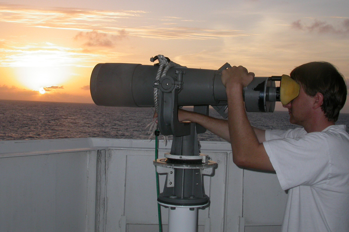 A scientist looking through a large set of binoculars, viewing marine mammals.