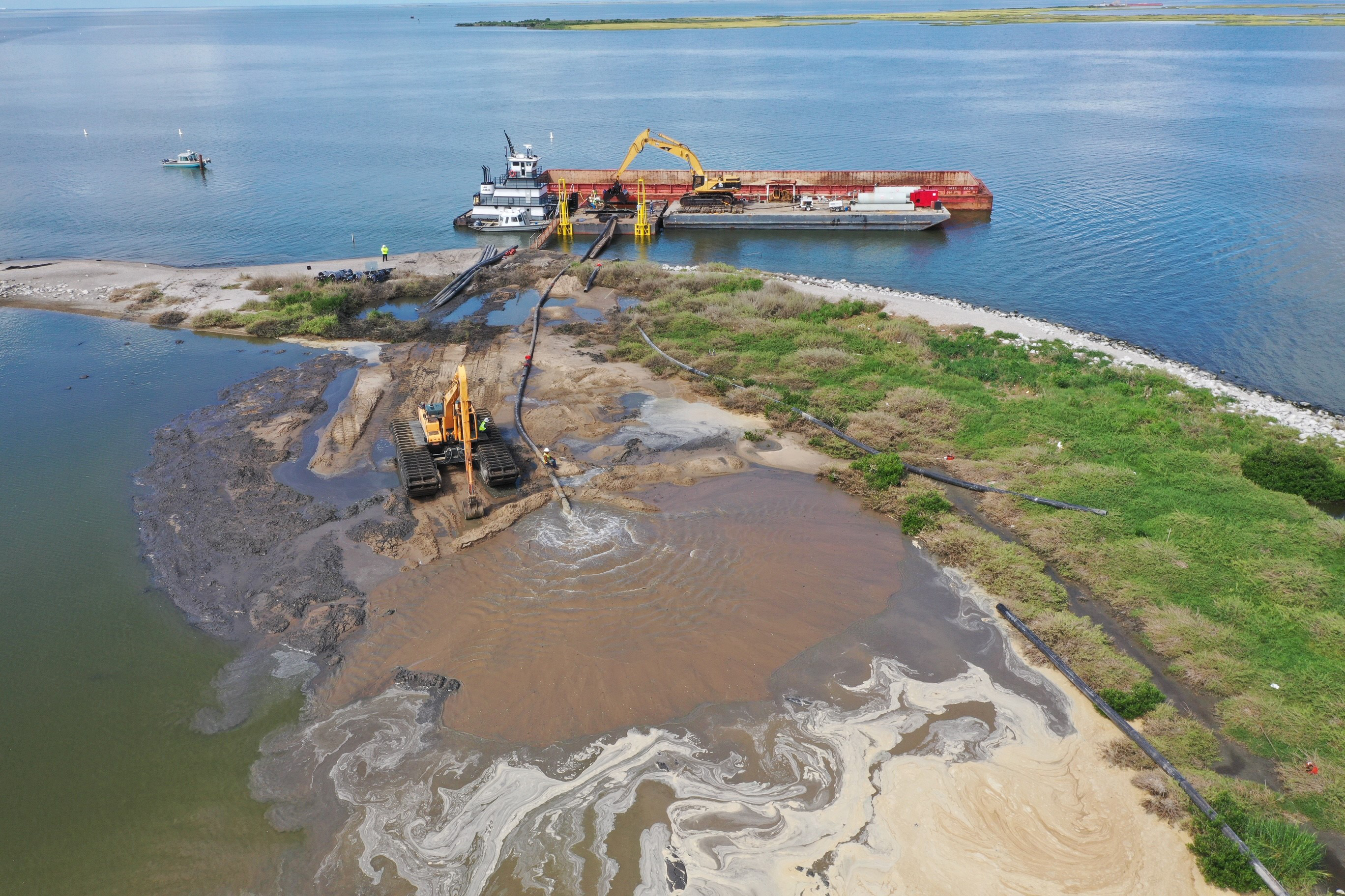 Equipment delivers sand onto a sliver of an island in the Gulf of Mexico.