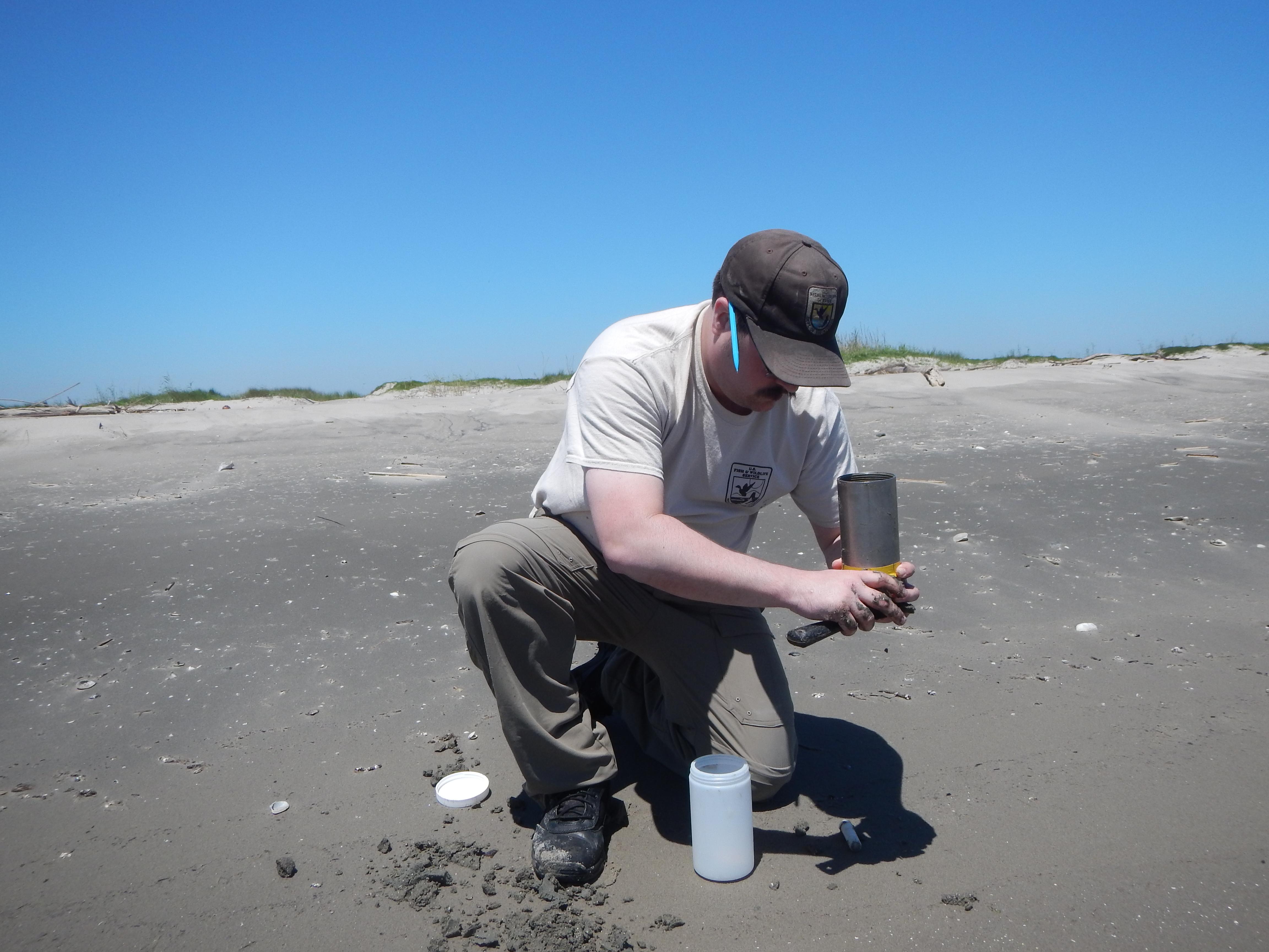A USFWS biologist takes samples of sand at North Breton Island.