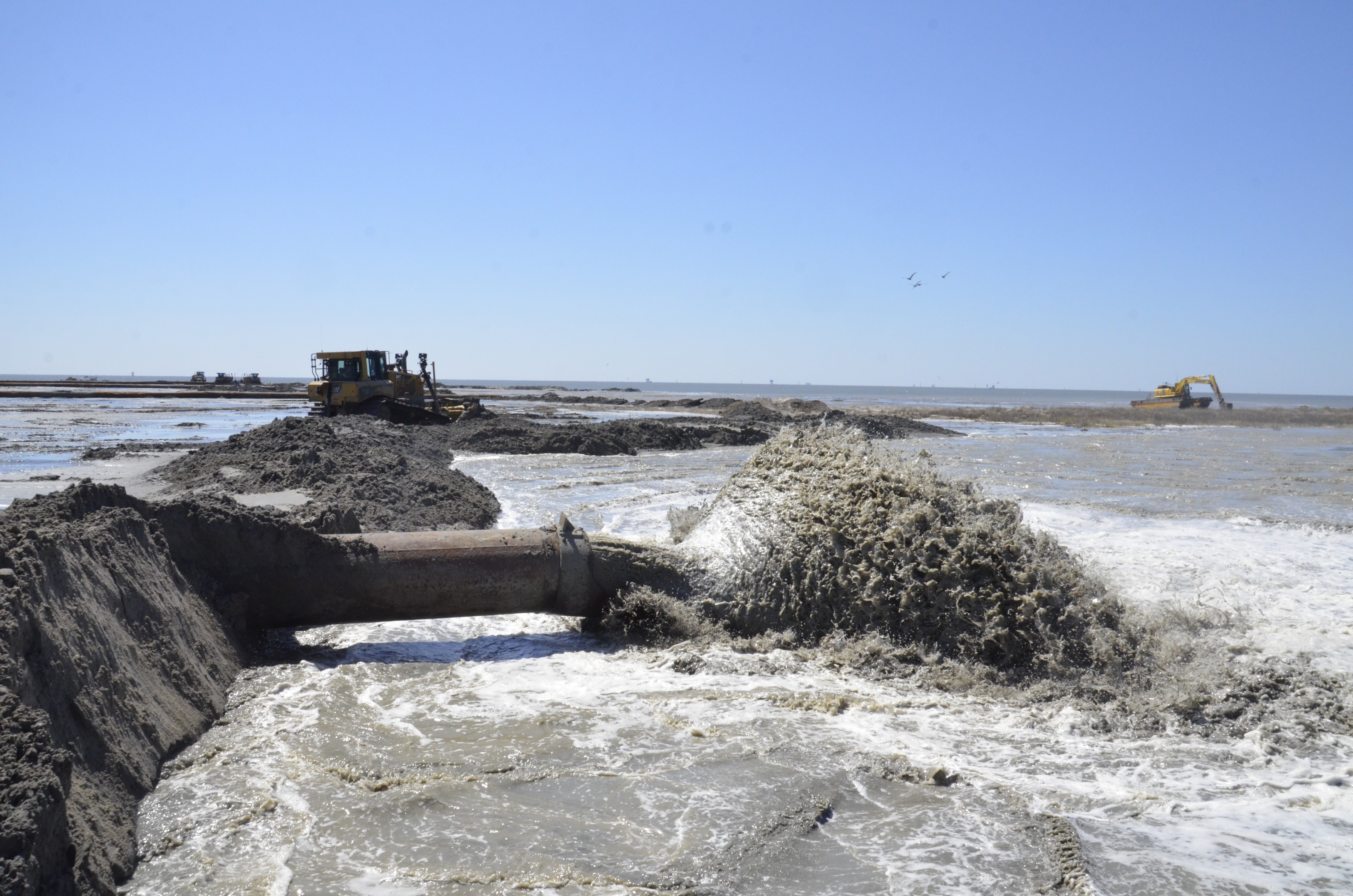 Dredged sediment pumping out of a pipe to help build coastal ecosystems.