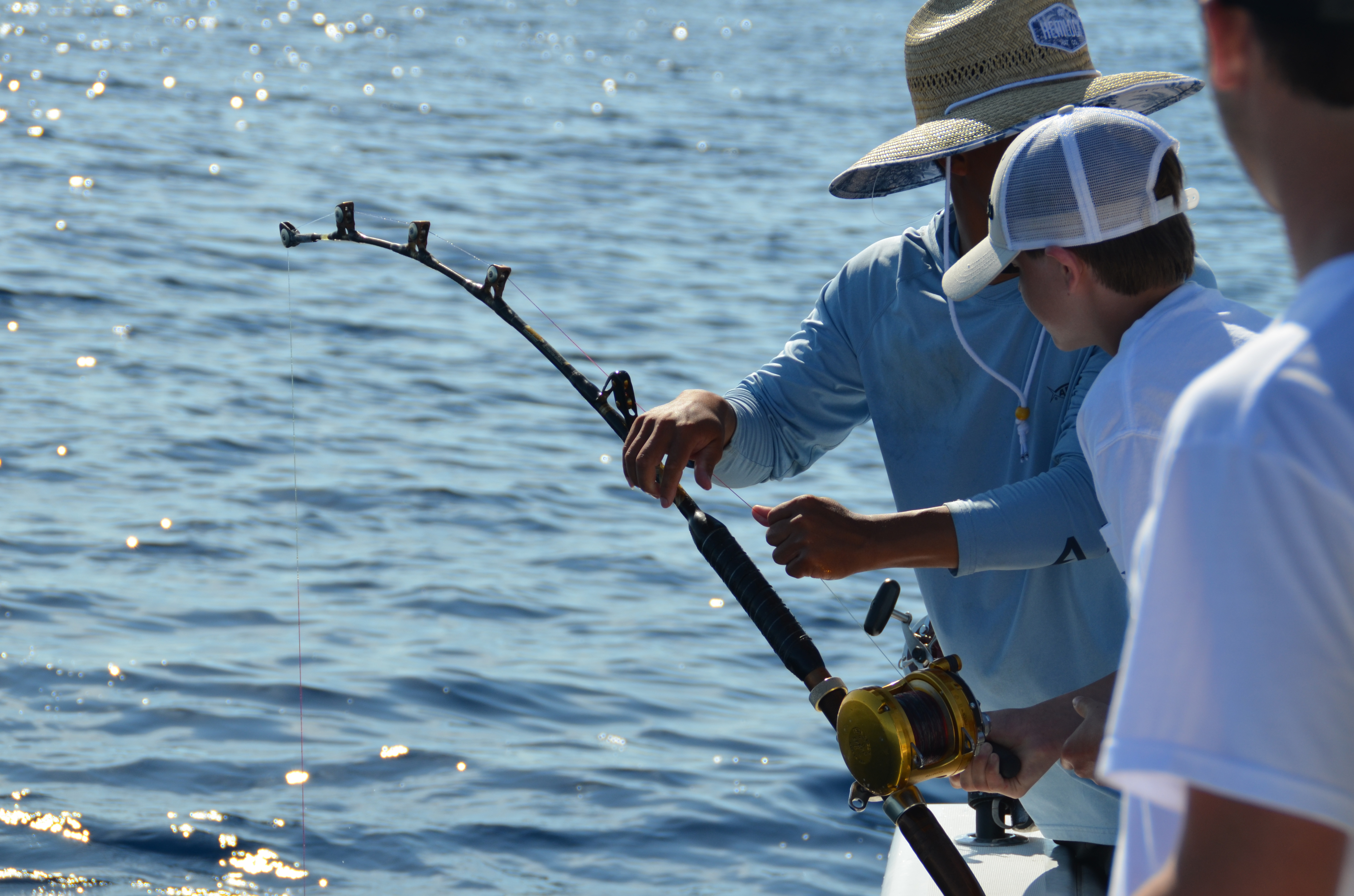 Three anglers on a boat with a fishing rod that's bending and looks to have a fish on.