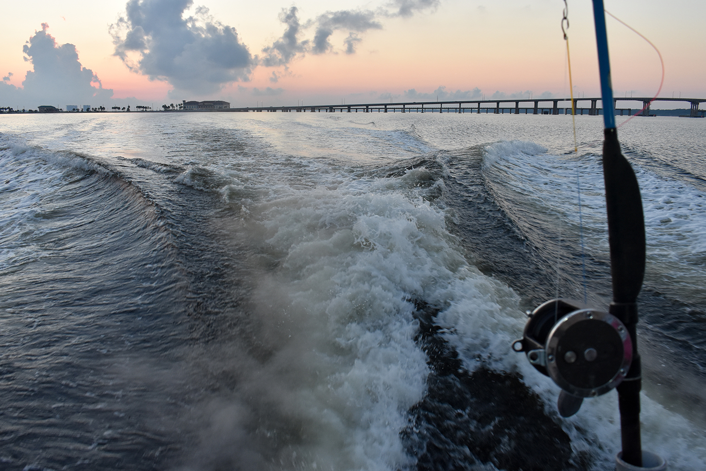 Bridge and coast can be seen from a boat. A fishing reel and pole is in the foreground, in front of the boat's wake. Image: Florida Fish and Wildlife