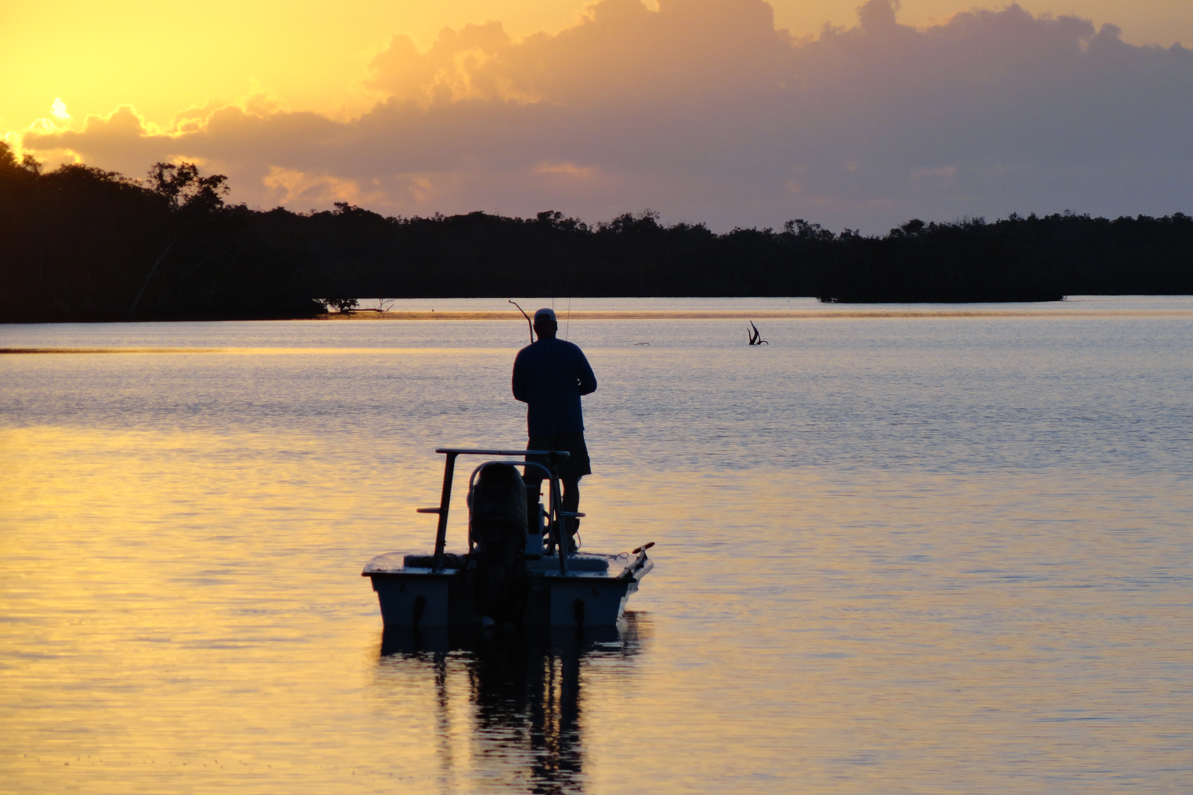 Silhouette of an angler fishing from a small boat on a lake with the sun setting in the background.